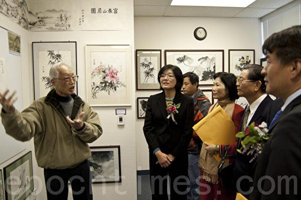 圣地亚哥北郡文教中心汉字文化节书法国画展上,吴伟(左一)向观众介绍他临摹的国书《富春山居图》。(杨婕/大纪元)