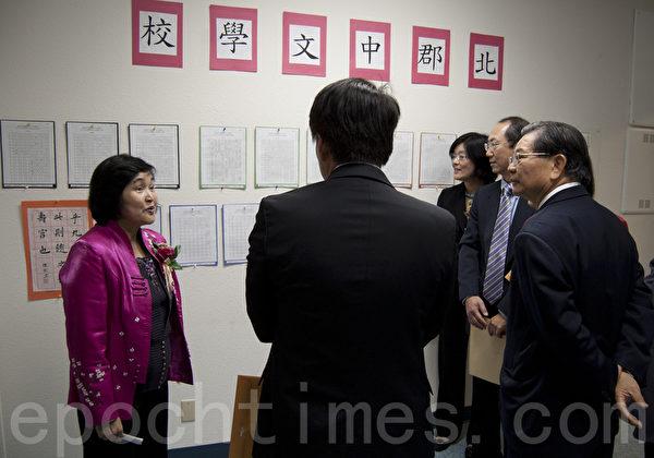 圣地亚哥北郡文教中心汉字文化节书法国画展上,徐钰铃(左一)向来宾介绍中文学校学生硬笔比赛和书法作品。(杨婕/大纪元)