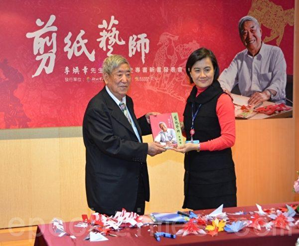 文化局副局长于玟赠送新书给国宝级剪纸大师李焕章老师.(宋顺澈/大纪元)