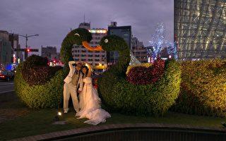 高雄捷運美麗島站4號出口的「愛心天鵝」藝術造景,天鵝曼妙姿態與新人幸福的身影,交織成愛心的型態。(高雄觀光局提供)
