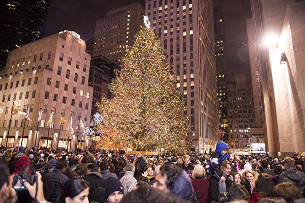 纽约浪漫圣诞夜,洛克菲勒中心人如潮涌。人们争相在圣诞树前留影。(戴兵/大纪元)