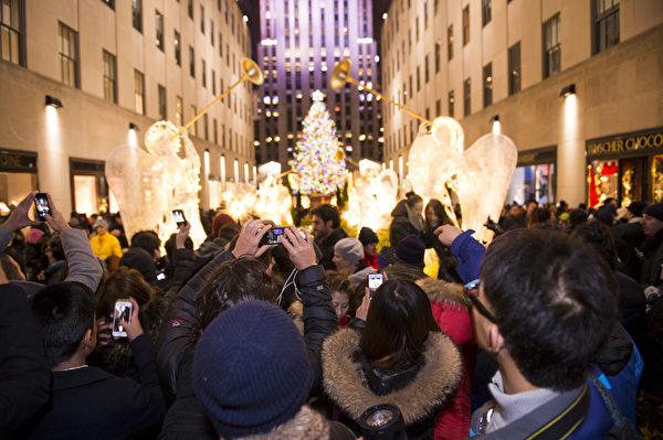 纽约浪漫圣诞夜,人们争相在洛克菲勒中心圣诞树前留影。(戴兵/大纪元)