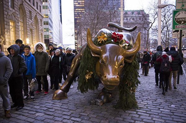 纽约浪漫圣诞夜,游客排队等候与华尔街铜牛合影。(戴兵/大纪元)
