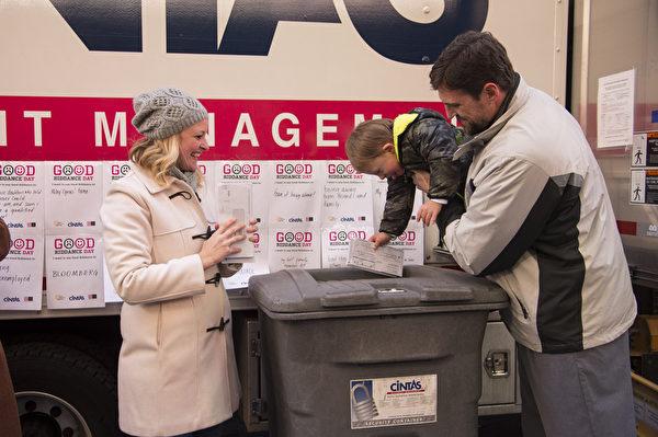 纽约时代广场告别2013,丢弃倒霉记忆。Amy Johnson和她的3岁的儿子Bodey特别受邀第一个把男孩的CAT扫描片子,医药账单等丢到碎纸机。Bodey患有唐氏综合症,2岁的时候被检查出得了癌症,通过化疗,症状得到减轻。(戴兵/大纪元)