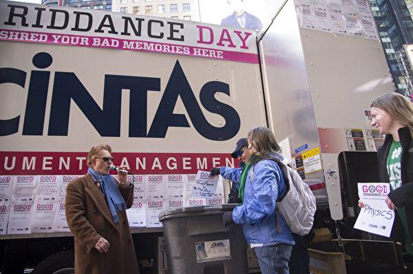 2013年12月28日,纽约时代广场,民众把造成不愉快的东西丢进碎纸机,象征性洗掉不好回忆、迎接崭新未来。(戴兵/大纪元)