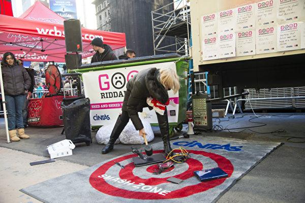 2013年12月28日,纽约时代广场,民众销毁造成不愉快的东西,象征性洗掉不好回忆、迎接崭新未来。(戴兵/大纪元)