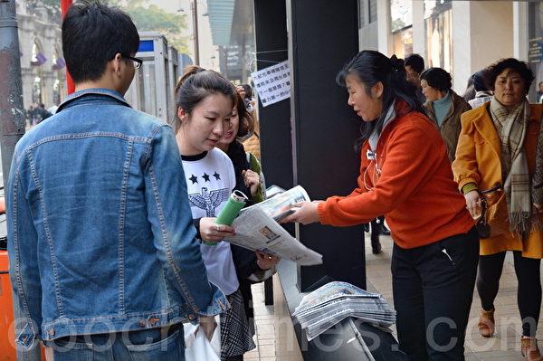 新年将近,许多大陆人来港购物,经过海港城广东道争拿大纪元报纸。(宋祥龙/大纪元)