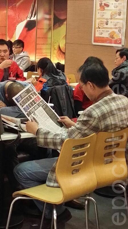 大陆游客看《大纪元》非常入神。连吃饭的空闲时间也不放过。(陈惜玲/大纪元)