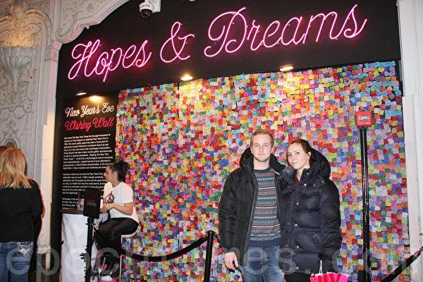 來自瑞典的克里斯托弗(左)及其未婚妻(右)特意來到紐約慶祝新年前夜,他寫在彩紙上的願望是與所愛永遠在一起。(攝影:王依瀾/大紀元)