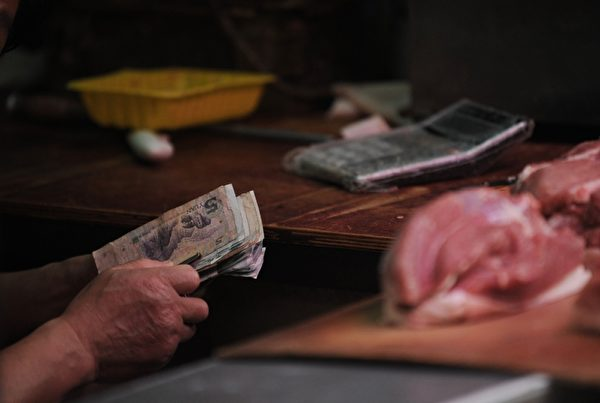 由於中共對貨幣及匯率的管制,導致人民幣出現外升內貶的怪現象。廣義貨幣8年增超三倍,人民幣購買力縮水近半,民眾感歎人民幣越來越不值錢。(PETER PARKS/AFP/Getty Images)