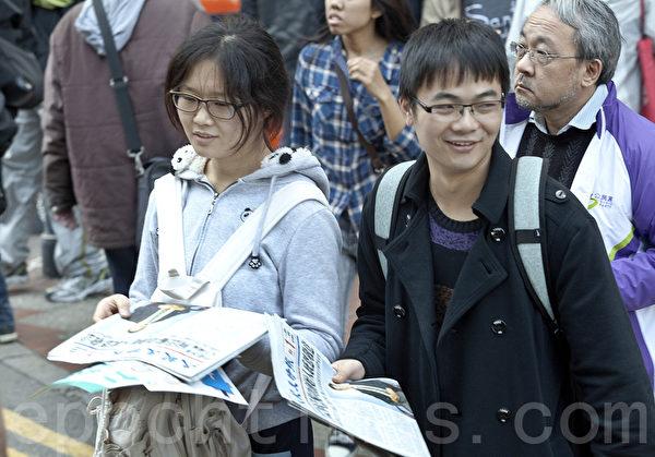 香港2014年新年大遊行於1月1日下午3時正式在維多利亞公園出發。大陸遊客也爭相拿大紀元時報,了解真相。(余鋼/大紀元)