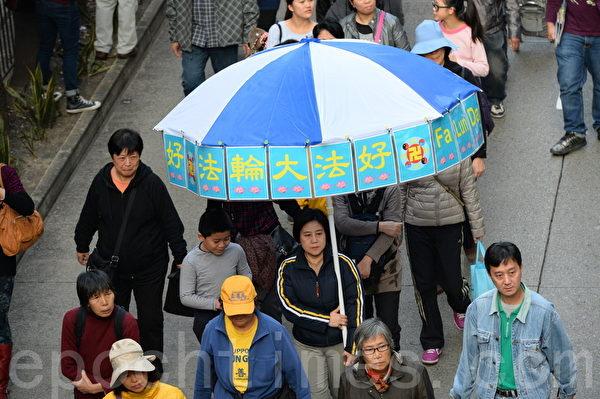2014年香港新年大遊行,法輪功學員帶著自製的法輪大法好的標語傘來參與遊行。(宋祥龍/大紀元)