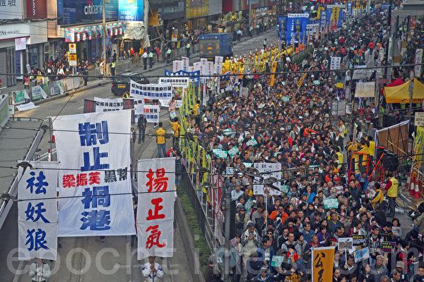 香港民间人权阵线举行的2014年新年大游行,3万人参加,法轮功的游行队伍以雄壮的天国乐团演奏及各式接揭露中共迫害和退党的幡旗横额,成为最受瞩目的阵列。(潘在殊/大纪元)