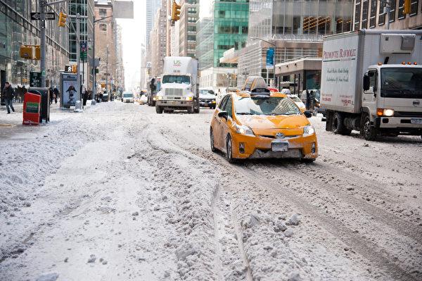 纽约遭受暴风雪袭击 罕见低温。车辆在第六大道艰难行驶。(戴兵/大纪元)