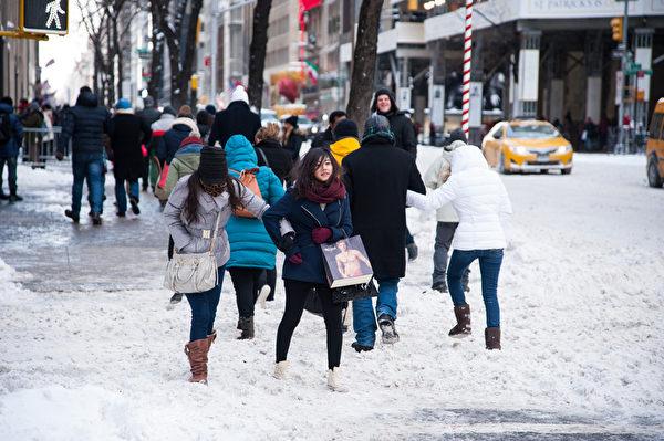 纽约遭受暴风雪袭击,罕见低温,积雪给行人带来不便。(戴兵/大纪元)