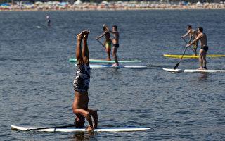 1月4日,巴西里约热内卢的科帕卡巴纳海边玩站立桨的众人中,一男子倒立在桨板上。(YASUYOSHI CHIBA/AFP)