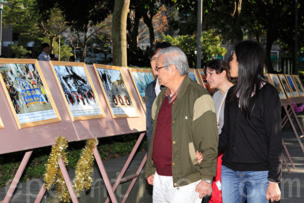 2014年1月11日,台湾台北法轮大法学员,群聚台北101前的信义广场向法轮大法创始人李洪志先生拜年。同时间也进行集体合唱、炼功与洪法活动。图为洪法图片展。(罗正恒/大纪元)