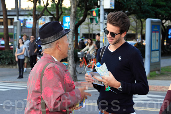 2014年1月11日,台湾台北法轮大法学员,群聚台北101前的信义广场向法轮大法创始人李洪志先生拜年。同时间也进行集体合唱、炼功与洪法活动。图为法轮功学员张山河(左)向海外游客传递法轮大法美好的讯息。(罗正恒/大纪元)