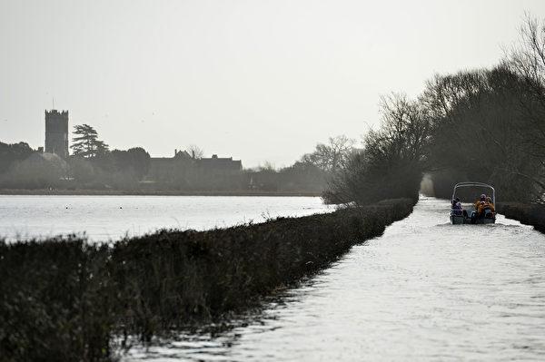 2014年1月26日,英國西南部薩默塞特郡(Somerset),洪水氾濫道路被淹,一艘小船運送受困民眾。(BEN STANSALL/AFP)