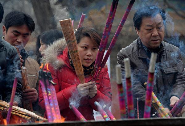 1月31日大年初一早上,大陸各地成千上萬的徹夜排隊的香客紛紛搶燒頭柱香。圖為,北京白雲觀民眾在燒香祈福。(MARK RALSTON/AFP/Getty Images)