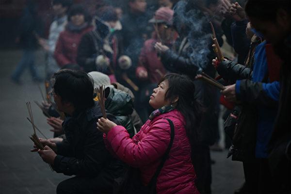 1月31日大年初一早上,大陸各地成千上萬的徹夜排隊的香客紛紛搶燒頭柱香。圖為,北京雍和宮民眾在燒香祈福。(Photo by Feng Li/Getty Images)