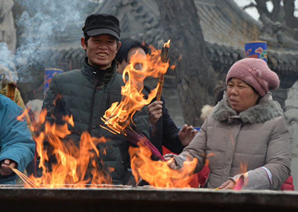 1月31日大年初一早上,大陸各地成千上萬的徹夜排隊的香客紛紛搶燒頭柱香。圖為,北京東岳廟民眾在燒香祈福。(Photo credit should read MARK RALSTON/AFP/Getty Images)