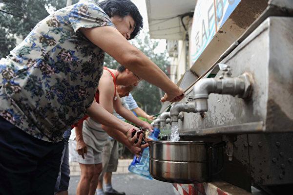 """北京市人均年水资源量甚至不足100立方米,而国际标准是人均500立方米为极度缺水。北京市的缺水程度甚至超过以干旱著称的中东和北非地区,""""比沙漠还缺水""""。图为北京居民正在盛装饮用水。(ChinaFotoPress/Getty Images)"""