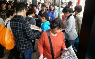 中國新年期間,大批大陸遊客擠爆香港。他們街頭巷尾拿大紀元閱讀,成為香港一大特殊景象。(大紀元圖片)