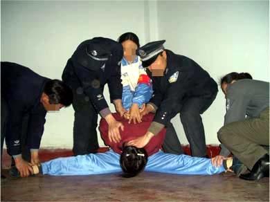 酷刑演示:強行將受害者的雙腿一字劈開 (圖片來源:明慧網)