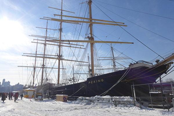 """位于华尔街和唐人街步行范围内的17号码头,原来是纽约最早的港口,有三百多年的历史。码头停泊着由三艘古老帆船搭建的博物馆,其中一艘""""北京号""""(Peking)是1911年建造的当时世界第二大帆船,岸边百米内还有一个水泥砌成的泰坦尼号纪念塔,是为纪念泰坦尼克号沉没一周年时建造的。由于其独特的地理位置和历史文化氛围,这里每年吸引上千万游客前来参观。近几年,大陆旅游团越来越多,一般都安排游客从这里的17号码头上船去自由岛观光自由女神像。(蔡溶/大纪元)"""