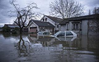 英國部份地區連日降雨,泰晤士河沿岸多地決堤,一些村莊被洪水淹沒。(Oli Scarff/Getty Images)