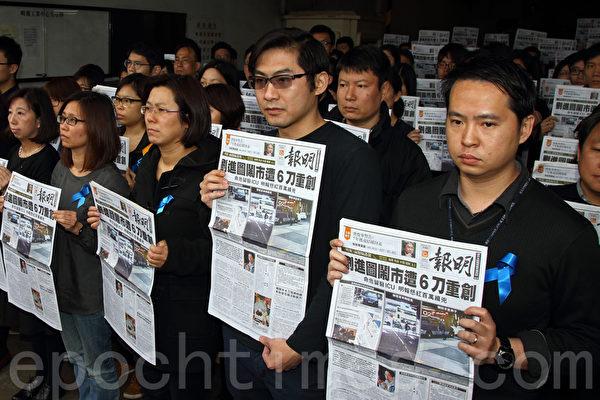 超过100名明报员工身穿黑衣,配戴蓝丝带,聚集在柴湾的公司门外,他们手持当天报导刘进图遇袭的报纸默站抗议,指明报报头转为黑色,是新闻界最黑暗的事。(潘在殊/大纪元)