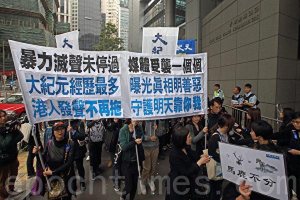"""继六千人出席记协反灭声游行创下了传媒举办游行的人数记录,事隔一周,在3月2日有双倍的市民-一万三千人站出来参加多个新闻团体联合举办的""""新闻界反暴力联席""""游行,誓言要追查刺杀明报前总编刘进图的真凶,捍卫新闻自由;香港大纪元时报的游行队伍再次深受瞩目和欢迎。(潘在殊/大纪元)"""