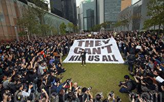近五百位新聞工作者、民主及建制派立法會議員、市民、新聞系學生身穿黑衣3月2日在中午12點齊集在添馬公園草地,出席由記協舉行的「新聞界-企硬-反暴力-默站行動」,他們在一幅寫著「They can」t kill us all」巨型橫幅上寫下對明報前總編輯劉進圖的祝福。他們放下手上的相機、筆記簿等採訪工具,默站五分鐘,以示對劉進圖先生遇襲的傷感、不滿。(潘在殊/大紀元)