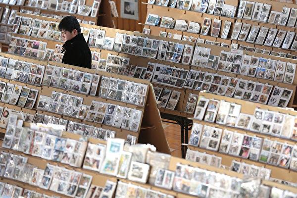 311东日本大地震三週年紀念日前夕,仙台市的一座體育館,一男子在大量被挽回的照片中尋找親人的遺照。(Yuriko Nakao/Getty Images)