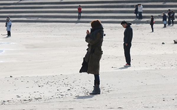 311东日本大地震三週年紀念日當天下午2:46,人們來到宮城縣七濱鎮海灘悼念亡靈。(Yuriko Nakao/Getty Images)