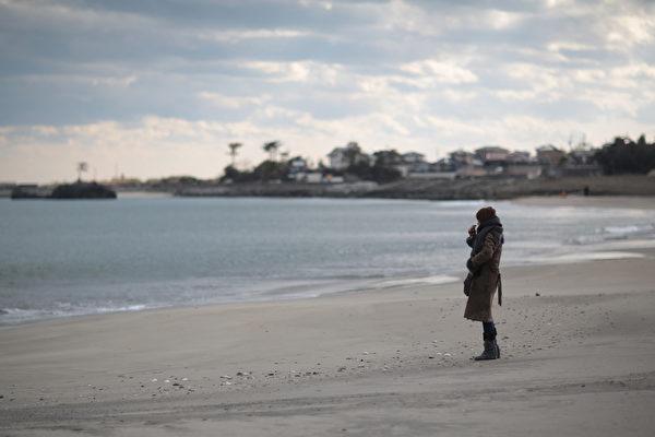 311东日本大地震三週年紀念日當天,宮城縣七濱鎮海灘,一女子在下午2:46默哀片刻後擦拭眼淚。(Yuriko Nakao/Getty Images)