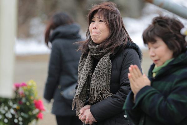 311东日本大地震三週年紀念日當天,在受災慘重的石卷市參加紀念活動的女子。(Yuriko Nakao/Getty Images)