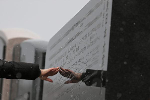 311东日本大地震三週年紀念日當天,受災慘重的石卷市,一女子伸手觸摸著刻有遇難者名字的石碑,緬懷故人。(Yuriko Nakao/Getty Images)