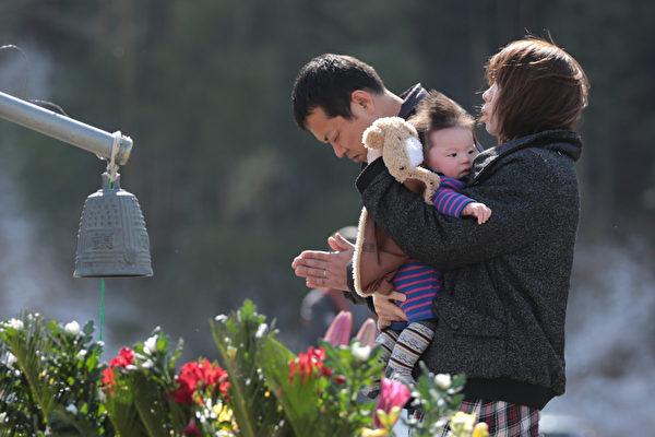 311东日本大地震三週年紀念日當天,受災慘重的石卷市一所小學前,一家人爲亡靈默哀。(Yuriko Nakao/Getty Images)
