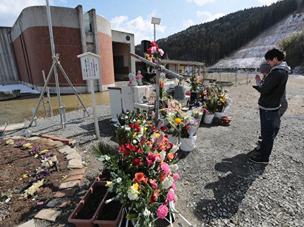311东日本大地震三週年紀念日當天,受災慘重的石卷市一所小學前,擺放著悼念亡靈的鮮花。(Yuriko Nakao/Getty Images)