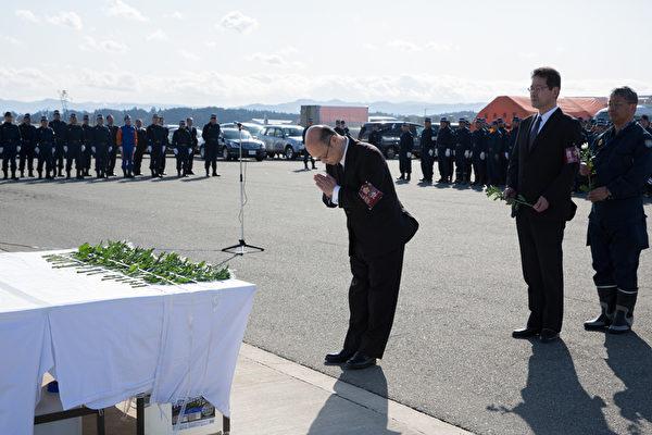 311东日本大地震三週年紀念日當天,一名警察在福島舉行的一個紀念活動中爲災民祈福。(Ken Ishii/Getty Images)