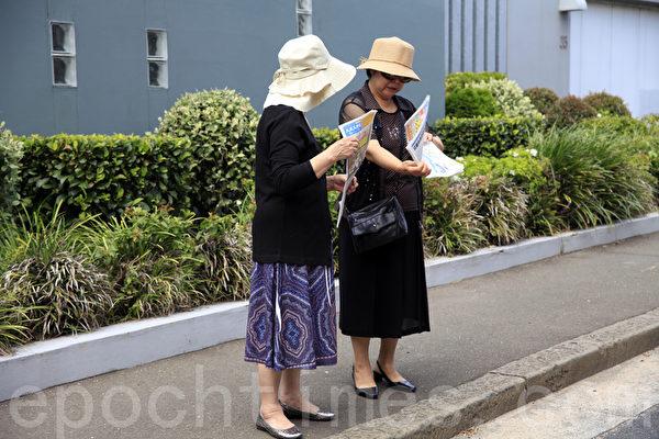 3月11日上午,在澳洲悉尼中领馆前,举办了揭露中共干扰神韵在悉尼演出的新闻发布会,希望中共能够认清事实,切勿在澳洲这个民主自由的国度再次侵犯人权。图为索取真相资料的华人。(袁丽/大纪元)