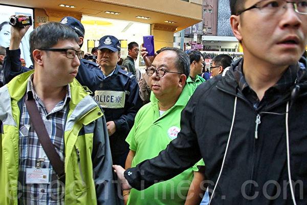 青关会副会长林国安被多名正义香港市民上前指骂,要靠多名警员保护。(潘在殊/大纪元)