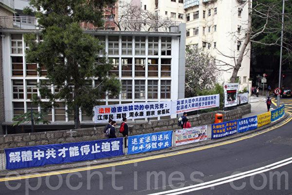 法輪功學員在港大正門外掛起揭露黃潔夫的橫額,引來不少學生觀看。(潘在殊/大紀元)