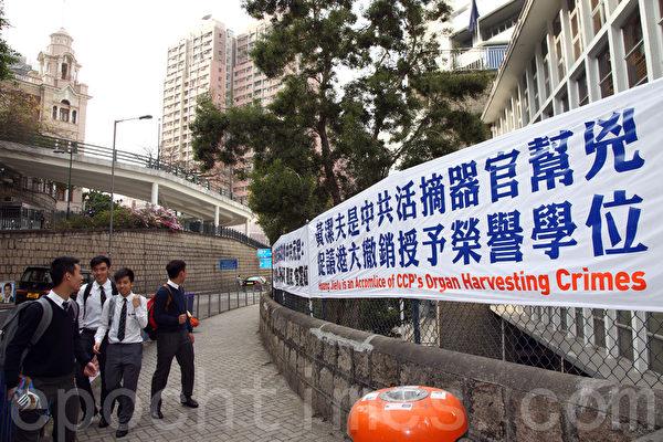 法轮功学员在港大正门外挂起揭露黄洁夫的横额,引来不少学生观看。(潘在殊/大纪元)