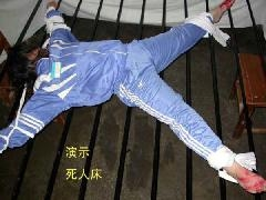 2011年7月13日辽宁省女子监狱将刘志抬到硬木床上,手、脚呈大字型绑住,上了一个星期的抻刑。刘志的手被抻得紫黑,尾骨被磨破了。之后刘志瘫痪,生活不能自理。图为,酷刑模拟图。(明慧网)