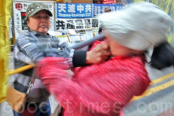 3月22日星期六,身穿便服的青关会女成员陶桂香(左)挥拳殴打法轮功学员(右),并把她推倒在地,再作势用手臂垫著头部倒地,然后抱头假装昏倒,试图栽赃法轮功学员。(潘在殊/大纪元)