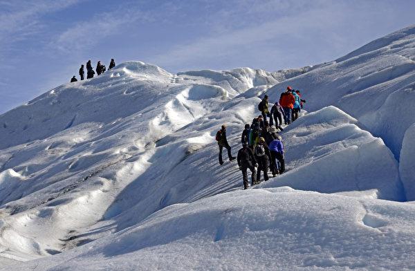 游客跋涉阿根廷冰川国家公园内的莫雷诺冰川。(MARIO GOLDMAN/AFP)