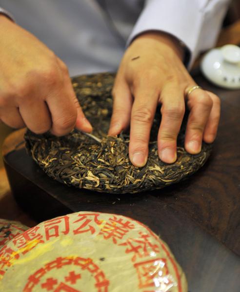 用工具从已制好的茶饼上把茶剥下来,准备泡茶。(图/Getty Images)